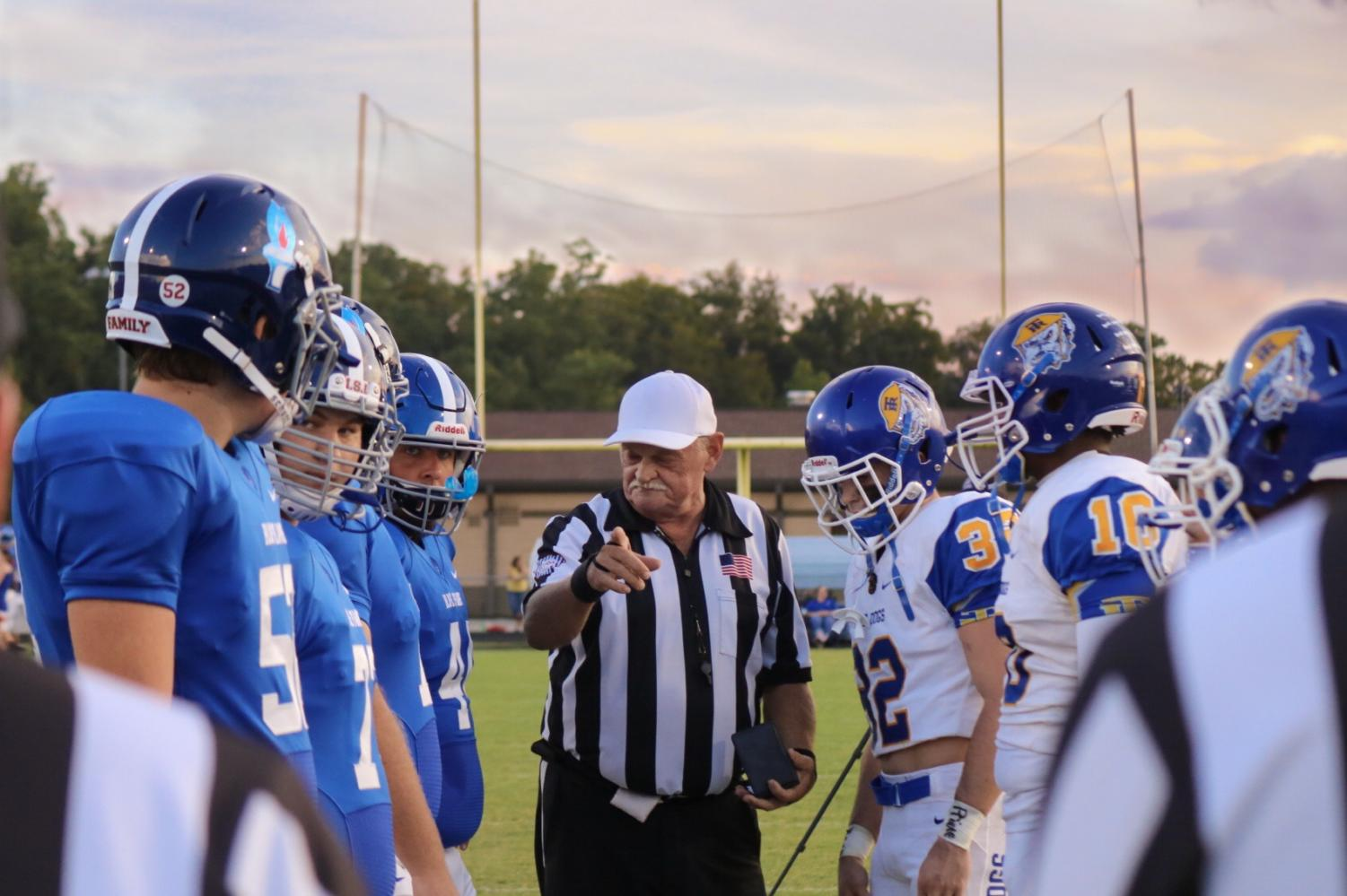 Referee addresses team captains during coin toss.